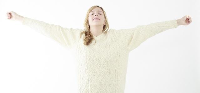 縮んだセーターを伸ばした女性