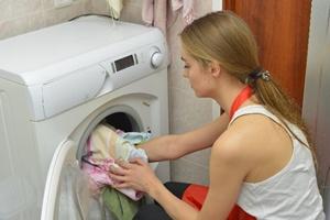 適量の洗濯物を入れる女性